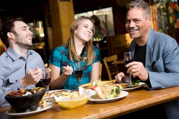 Young couple with older man eating Mexican and laughing